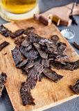 Beef jerky on wood board and beer Stock Photography