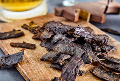 Beef jerky on wood board and beer Stock Images