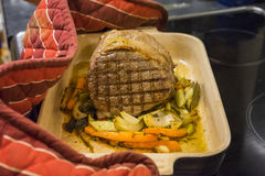 Beef joint ready to go into the oven. Vegetables underneath with oven gloves holding. Beef joint in a tray ready for the oven. Dinner time food. Home cooking stock photo