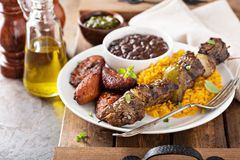 Beef kebab with rice, beans and fried plantains stock images