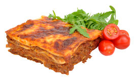 Beef Lasagne With Lettuce And Tomatoes. Portion of beef lasagne with fresh lettuce and tomatoes isolated on a white background stock images