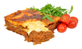 Beef Lasagne With Lettuce And Tomatoes. Portion of beef lasagne with fresh lettuce and tomatoes isolated on a white background royalty free stock photos