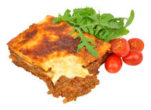 Beef Lasagne With Lettuce And Tomatoes. Portion of beef lasagne with fresh lettuce and tomatoes isolated on a white background stock image