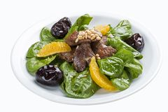 Beef liver with spinach and prunes. On a white plate. Lobio from green beans on a white plate on white background stock photo