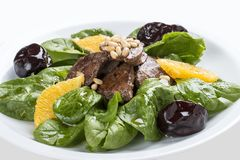 Beef liver with spinach and prunes. On a white plate. Lobio from green beans on a white plate on white background stock images