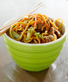 Beef lo mein in a bowl with chopsticks. Closeup photo of a bowl of beef lo mein in a bowl with chopsticks stock photography