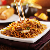 Beef lo mein with chopsticks. Eating chinese beef lo mein with chopsticks royalty free stock photos