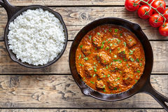 Beef Madras traditional slow cook Indian spicy chili lamb meat food with rice and tomatoes. In cast iron pan on vintage wooden table background. India culture stock images