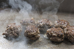 Beef meat balls cooking on grill at at restaurant buffet Royalty Free Stock Images