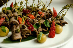 Beef meat roll with arugula, red currant and strawberry Stock Photo