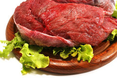 Beef meat and salad over white on plate. Red raw beef meat and salad over white on wooden plate Stock Image