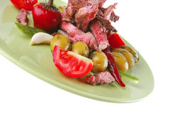 Beef meat slices on green. Dish over white Stock Photography