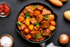 Beef meat stewed with potatoes and carrots. In cast iron pan on dark background, top view Stock Photo