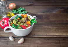 Beef meat stewed with vegetables in ceramic pot with ingredients on wooden background Stock Images