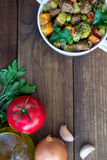Beef meat stewed with vegetables in ceramic pot with ingredients on wooden background Royalty Free Stock Photography