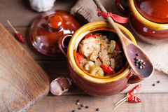 Beef meat stewed with vegetables in ceramic pot. On a wooden background Royalty Free Stock Images