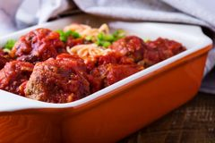 Beef meatballs with spaghetti in marinara sauce. Homemade beef meatballs with spaghetti in marinara sauce served in baking dish on rustic wooden table stock images