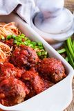 Beef meatballs with spaghetti in marinara sauce. Homemade beef meatballs with spaghetti in marinara sauce served in baking dish on rustic wooden table royalty free stock photography
