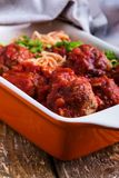 Beef meatballs with spaghetti in marinara sauce. Homemade beef meatballs with spaghetti in marinara sauce served in baking dish on rustic wooden table royalty free stock image
