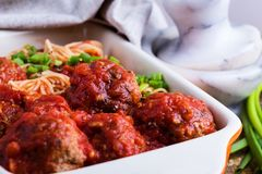 Beef meatballs with spaghetti in marinara sauce. Homemade beef meatballs with spaghetti in marinara sauce served in baking dish on rustic wooden table stock photo