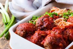 Beef meatballs with spaghetti in marinara sauce. Homemade beef meatballs with spaghetti in marinara sauce served in baking dish on rustic wooden table stock photography