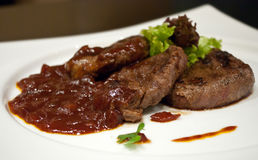 Beef medallions. With tomato sauce and greens Stock Photo