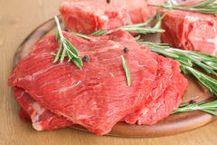 Beef Medallions with Rosemary. Beef Medallions Marinated with Rosemary and Peppercorns on Cutting Board Royalty Free Stock Photos