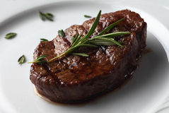 Beef meet with rossmary in a white plate.  Stock Image