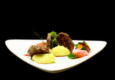 Beef mignon with mashed potato. Grilled beef filet mignon steak with mashed potato, vegetables and salad on triangle plate isolated on black background. Modern stock photo