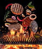 Beef milled meat on hamburger with vegetables and spices fly over the flaming grill barbecue fire royalty free stock images