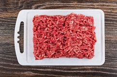 Beef mince on cutting board on dark wooden table. Beef mince on plastic cutting on dark wooden table. Top view Stock Photos