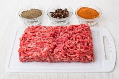 Beef mince, red and black pepper, carnation on wooden table. Beef mince on plastic cutting board, bowls with red and black pepper, carnation on wooden table Stock Photo