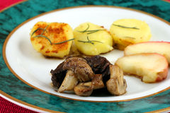 Beef with mushrooms. Beef with mushroom with sauted apples and potatoes sprinkled with rosemary Stock Photography