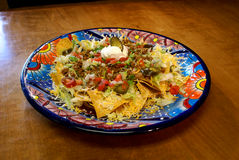 Beef Nachos in Festive Mexican Plate. Mexican Nacho chips covered with ground beef, shredded cheese, tomatoes, green bell peppers, jalapenos, and sour cream Stock Image