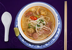 Beef Noodle Soup. Hot noodle soup with rare beef, lemon and red hot chili royalty free stock photography