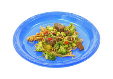 Beef and noodle stir fry on blue plate Stock Images