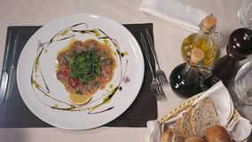 Beef o fish carpaccio with parmesan, lemon and arugula in modern restaurant, top view stock video footage