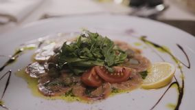 Beef o fish carpaccio with parmesan, lemon and arugula in modern restaurant, top view stock video