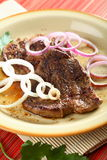 Beef with onion on the plate Stock Photos