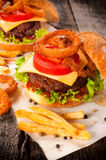 Beef and onion rings. Beef burger with onion rings and french fries.Selective focus on the beef burger Stock Photos