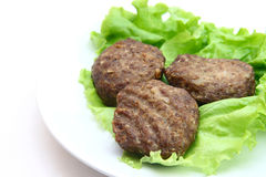Beef Patty with lettuce on white background. Beef Patty steamed with lettuce on white background Royalty Free Stock Photos