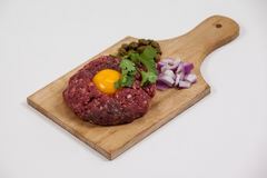 Beef patty, onions and olives on wooden board. Against white background Stock Photo