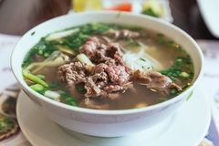 Beef Pho is a Vietnamese soup consisting of broth, rice noodles called bánh phở, a few herbs, and meat. stock photos