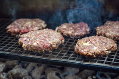 Beef or pork meat barbecue burgers for hamburger prepared grilled on bbq smoke grill, close up Royalty Free Stock Photos