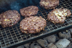 Beef or pork meat barbecue burgers for hamburger prepared grilled on bbq smoke grill, close up Royalty Free Stock Photography