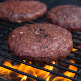 Beef or pork meat barbecue burgers for hamburger prepared grilled on fire flame grill Royalty Free Stock Photos