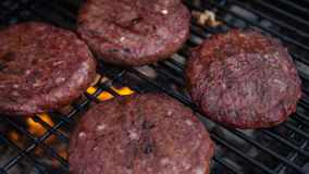Beef or pork meat barbecue burgers for hamburger prepared grilled on fire flame grill Royalty Free Stock Image