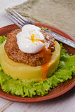 Beef and pork patty with poached egg, smashed potato and lettuce Stock Images