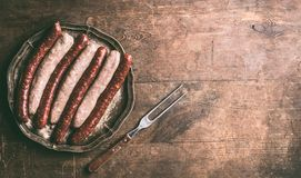 Beef and pork sausages for grill or bbq on dark vintage plate with meet fork on rustic wooden background. Top view. Place for your design, text or recipes royalty free stock photos