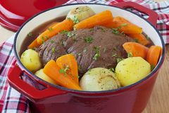 Beef Pot Roast in a Red Pot. Bolar roast, or blade roast, pot roasted with potatoes, onions and carrots. A simple, satisfying meal stock images